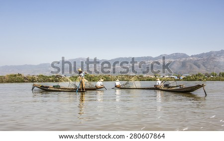 NIAUNGSHWE, MYANMAR - JANUARY 31, 2015: A legrowing fisherman at Inle lake is catching fish with a net . In the background are the floating gardens.