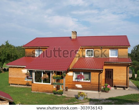NICA, LATVIA - AUGUST 12, 2010: Country house has red color metal roof and wooden walls.