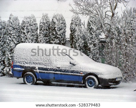 NICA, LATVIA - DECEMBER 3, 2016: After snowfall car in farm yard is covered with snow.