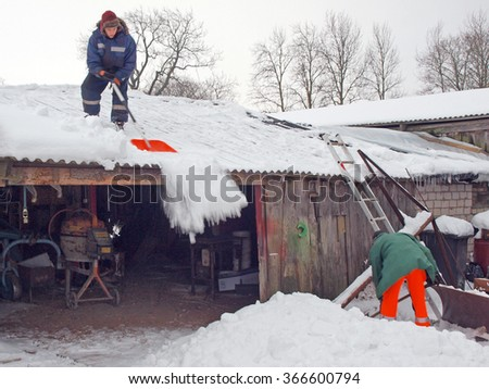 NICA, LATVIA - JANUARY 24, 2016: After snowfall country farmers are removing the snow from barn roof. - stock photo