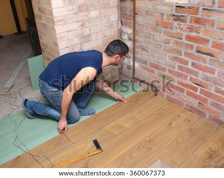 NICA, LATVIA - JANUARY 9, 2016: Construction worker is installing laminated floor in room.