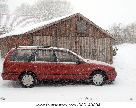 NICA, LATVIA - JANUARY 19, 2016: Red car is parked outdoors during snow storm near wooden barn.        - stock photo