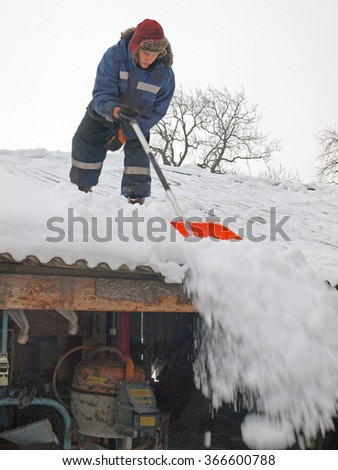 NICA, LATVIA - JANUARY 24, 2016: Young man country farmer is removing the snow from barn roof. - stock photo