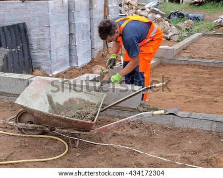 NICA, LATVIA - JUNE 8, 2016: Adult man construction worker is building house wall from foam concrete blocks. - stock photo