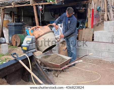 NICA, LATVIA - JUNE 13, 2016: Construction worker is making grout with cement mixer and filling in wheelbarrow. - stock photo