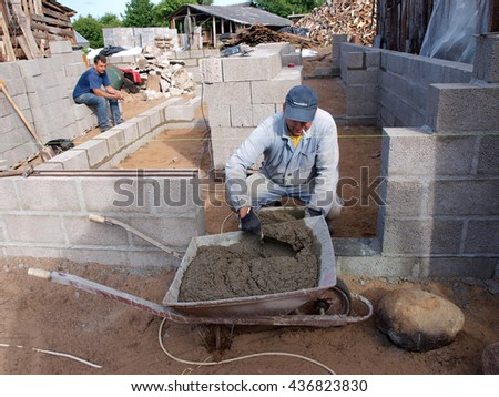 NICA, LATVIA - JUNE 13, 2016: Construction worker mason is taking grout with trowel from wheelbarrow.          - stock photo