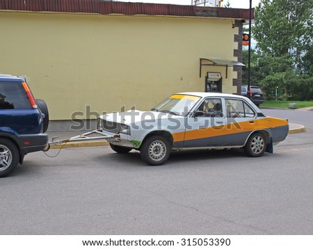NICA, LATVIA - JUNE 25, 2013: Damaged car is towing by hard triangle from metal tubes.     - stock photo