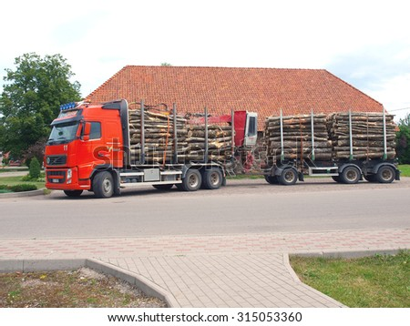 NICA, LATVIA - JUNE 25, 2013: Heavy forest truck with trailer is transporting wooden logs to port.       - stock photo