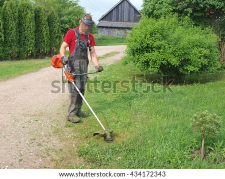 NICA, LATVIA - JUNE 8, 2016: Young man is cutting grass with string mower.