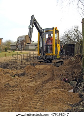 NICA, LATVIA - MARCH 21, 2009: Adult man worker is building grovel road in country farm yard with mini excavator.