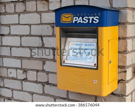 NICA, LATVIA - MARCH 2, 2016: Post office mailbox is hanging on council building wall near side entrance. - stock photo
