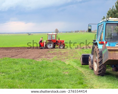 NICA, LATVIA - MAY 1, 2015: Farmers are planting potatoes with tractor powered potato planter.      - stock photo