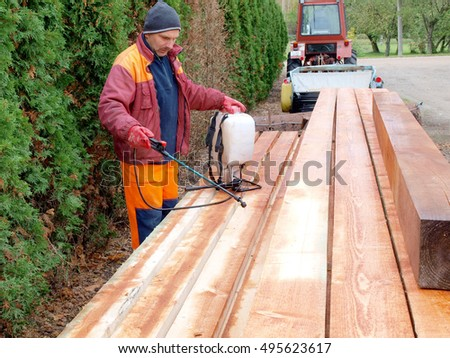 NICA, LATVIA - OCTOBER 9, 2016: Adult man worker is spraying preservative liquid on stacked timber boards beams and planks.