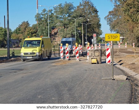 NICA, LATVIA - OCTOBER 15, 2015: Road asphalt repair is begun on way to Lithyania near bus stop.         - stock photo