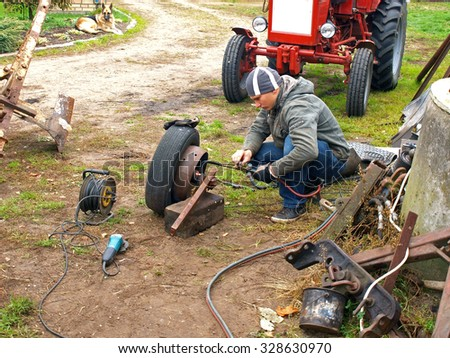 NICA, LATVIA - OCTOBER 17, 2015: Young man is cutting iron wheel detail with gas welding torch outdoor in yard.        - stock photo