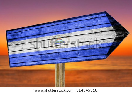 Nicaragua Flag wooden sign on beach background - stock photo