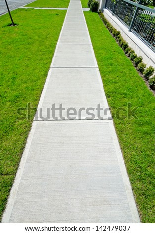 Nice and clean long, strait sidewalk, path at the empty street. Neighborhood scenery.