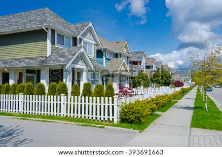 Nice and comfortable great neighborhood. Some homes behind white wooden fence on the empty street in the suburbs of Vancouver, Canada.