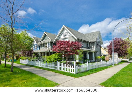 Nice and comfortable neighborhood. A row, line of the houses, homes behind white country style wooden fence in the suburbs of Canada, Vancouver. - stock photo