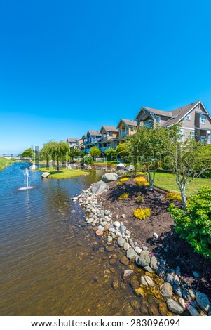 Nice and comfortable neighborhood, community. Some homes, town houses with nicely landscaped yard in the suburbs of the North America. Canada. - stock photo