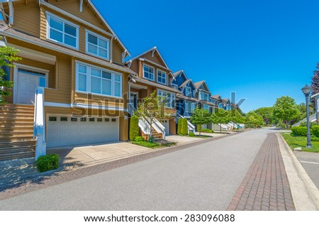 Nice and comfortable neighborhood, community. Some, line of homes, town houses on empty street in the suburbs of the North America. Canada. - stock photo