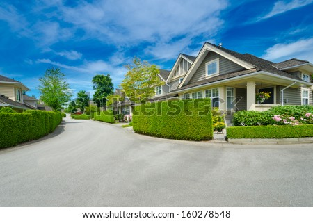 Nice and comfortable neighborhood. Houses  behind green fence on the empty street in the suburbs of Vancouver, Canada. - stock photo