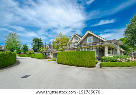 Nice and comfortable neighborhood. Houses behind nicely trimmed green fence on the empty street in the suburbs of Vancouver, Canada. Landscape design. - stock photo