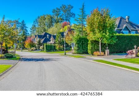 Nice and comfortable neighborhood. Houses on the empty street. - stock photo