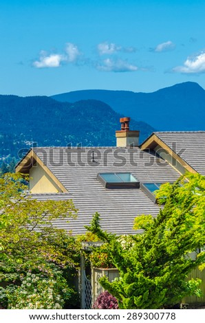 Nice and comfortable neighborhood.Roof of the house with great view at the mountains at the back in the suburbs of Vancouver, Canada. Vertical.
