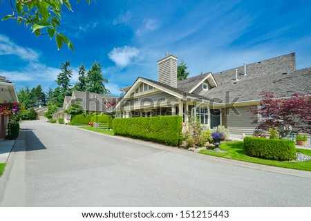 Nice and comfortable neighborhood. Some homes and garages on the empty street in the suburbs of the North America. Canada.