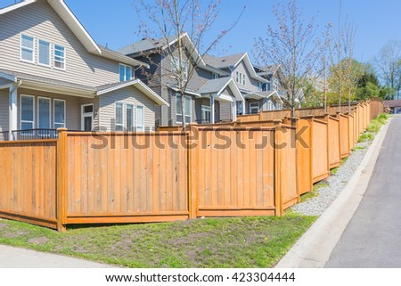 Nice and comfortable neighbourhood with custom built houses behind the fence in the suburbs of the North America. Canada. - stock photo