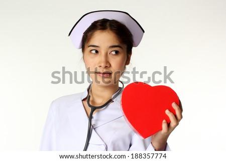 Nice asian nurse holding a symbol of heart  - stock photo