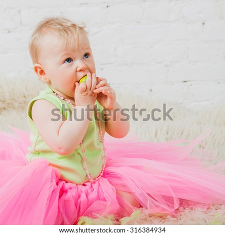 Nice baby girl eating green apple while sitting on floor