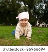 Nice baby girl in green meadow - stock photo