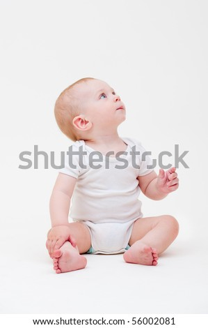nice baby in white t-shirt sitting on the floor and looking up