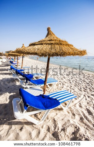 Nice beach with beach chairs and thatched umbrellas in Port El Kantaoui, Tunisia. - stock photo