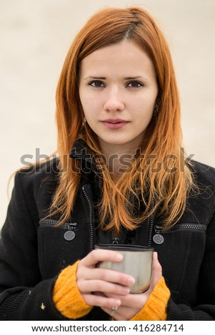 Nice,beautiful,freezing,cheerful,red-haired,glamorous,pretty girl,lady,person with sweet tea,warm tea,drink tea,love tea,like tea,heats with a cup of hot milk chocolate,tea,coffee,with cute smile,tea - stock photo
