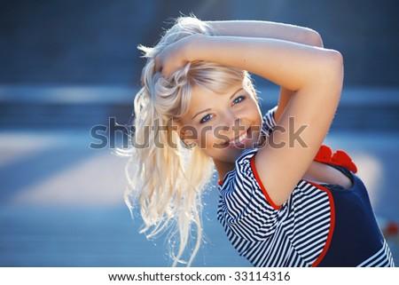 Nice beautiful woman wearing salor striped vest posing outdoors - stock photo