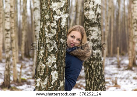 Nice, beautiful young lady hiding behind birch tree in the park - stock photo