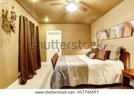 Nice bedroom with mocha interior paint and beige carpet. Also large wooden bed with perfect bedding