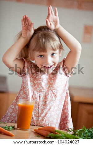 Nice blond baby girl with glass of carrot juice. She represents a hare.