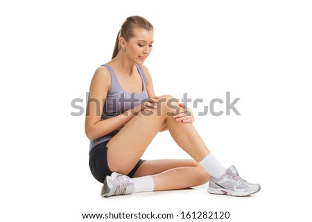 Nice blond girl feeling pain in her knee. Isolated on white  - stock photo