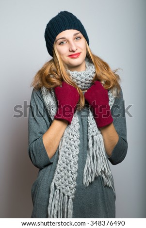 nice blonde girl in winter gloves, Christmas concept, studio photo isolated on a gray background - stock photo