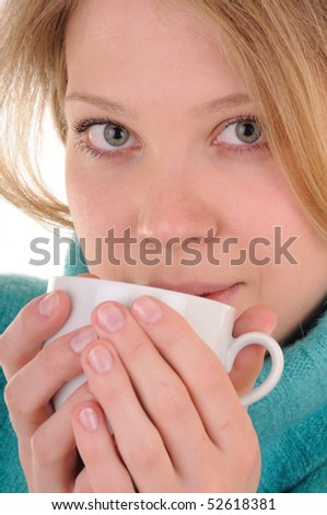 Nice blonde woman in sweater holds white cup with hot drink