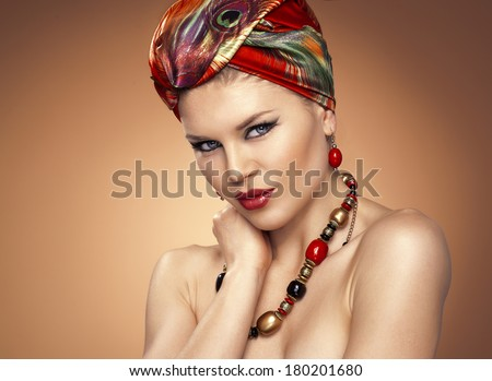 Nice blue eyed girl wearing african headdress and beautiful jewelery. Young attractive Caucasian woman model with professional ethnic make-up.   - stock photo