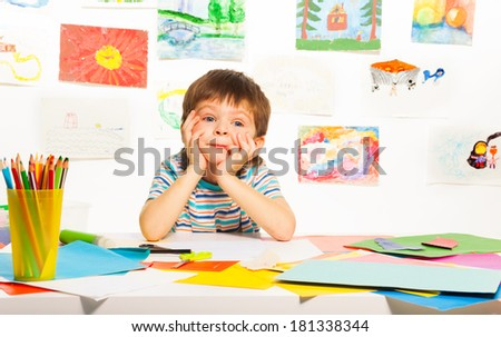 Nice bored three years old boy sitting in the class with images paper and pencils - stock photo
