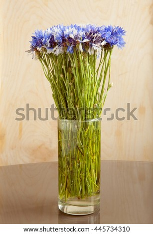 Nice bouquet of blue and white cornflowers in a simple glass as a vase standing on the reflective surface against a light textured wooden background - stock photo