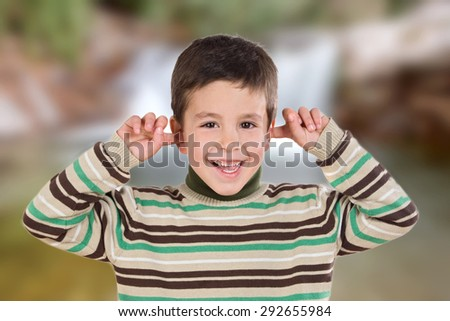 Nice boy covering the ears with unfocused background - stock photo
