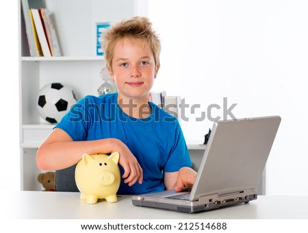 nice boy with laptop and piggy bank - stock photo