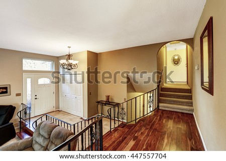 Nice bright entry way to home with high vaulted ceiling, hardwood floor and staircase  - stock photo